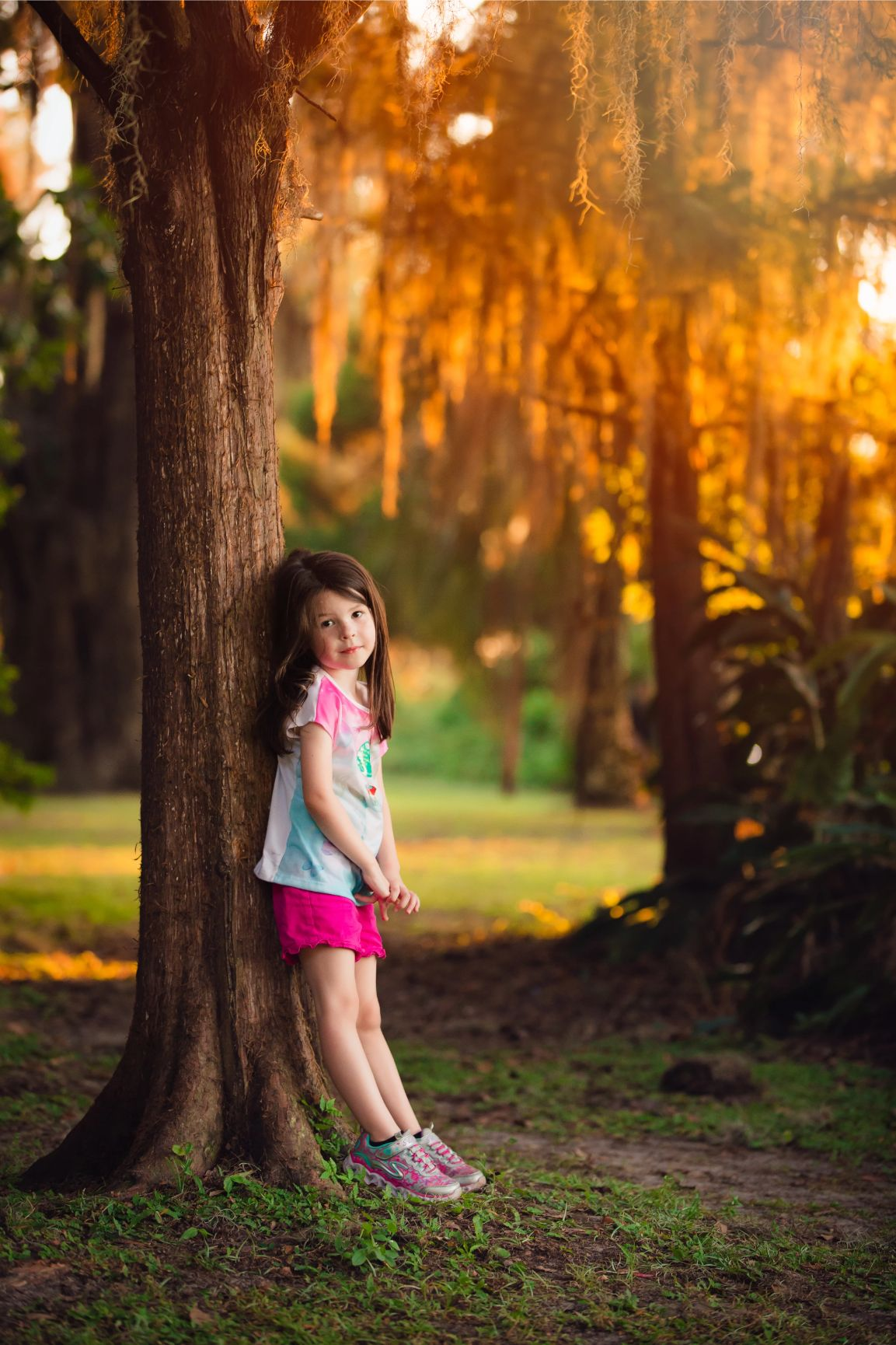 Portrait of little girl leaning against a tree during a family photos session at Alpine Groves Park