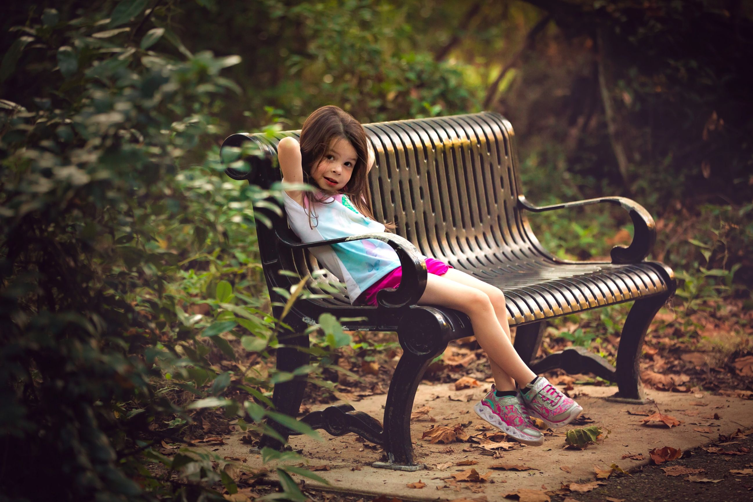 Photo of a little girl sitting on a bench during a photo shoot in Jacksonville Florida at Alpine Groves Park