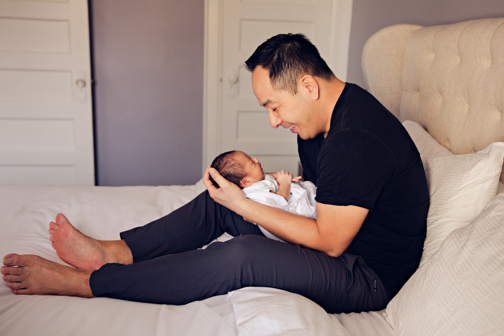 dad sitting on bed smiling down at newborn son