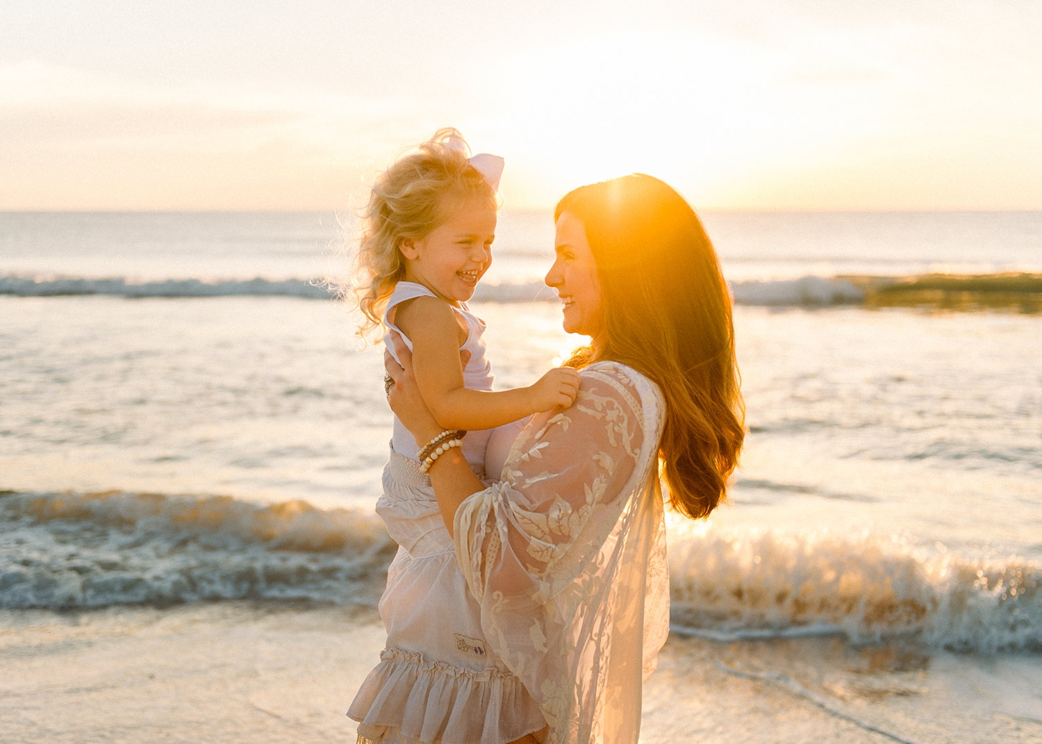 mom holding her daughter and smiling, the sun is rising over the Atlantic ocean