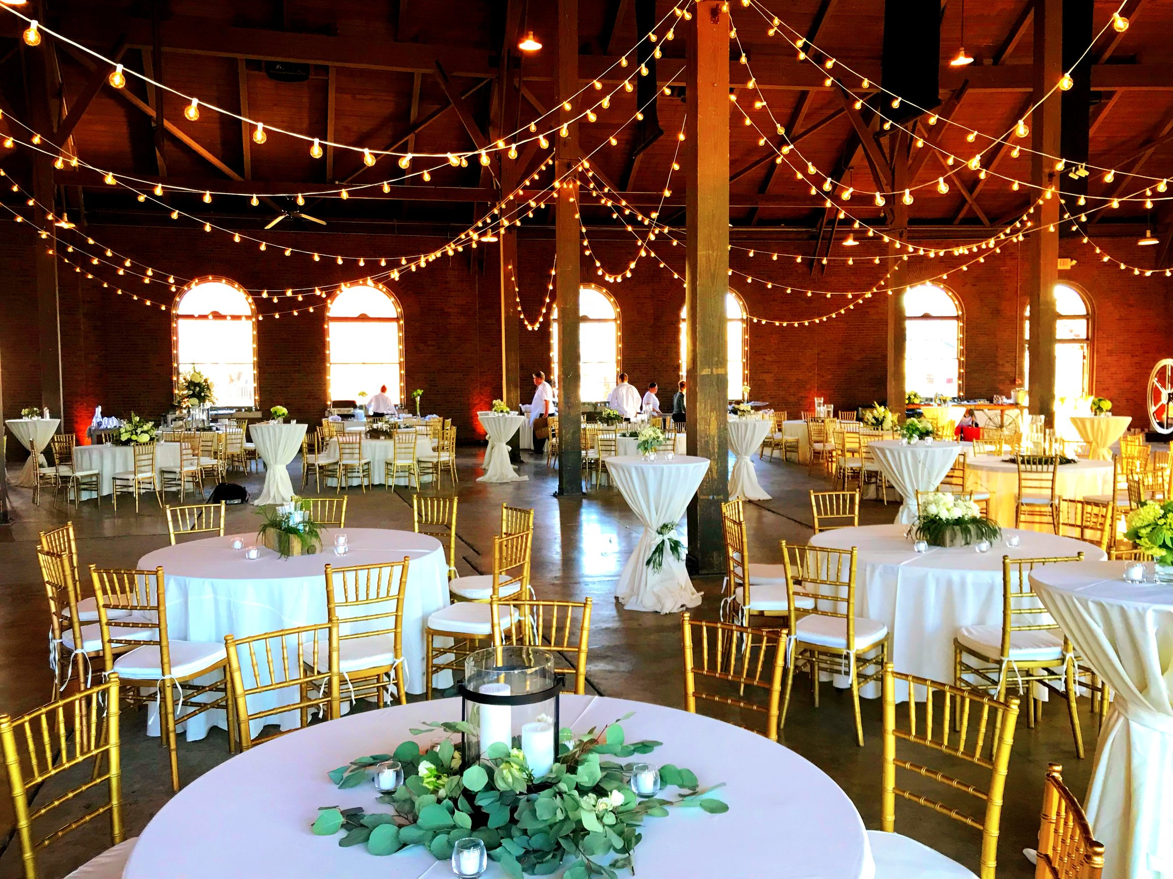 A beautiful wedding event at earlyworks the roundhouse in huntsville alabama with cafe string lights uplights spotlights and more provided by metropolitan