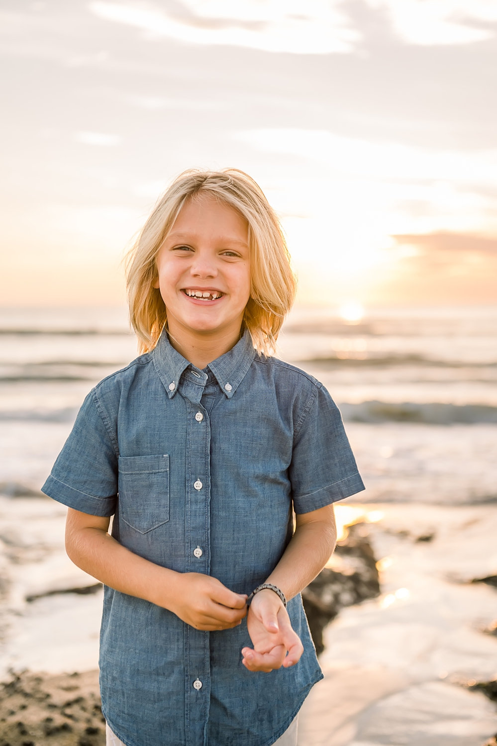 portrait of a little boy on Saint Augustine Beach, he is wearing a short sleeved denim shirt