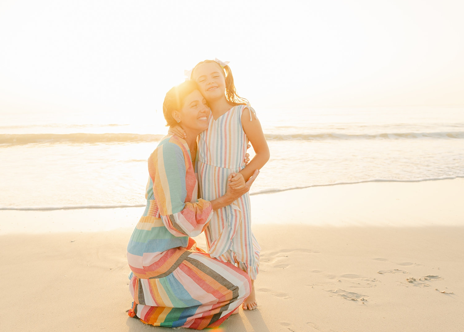 cancer survivor kneeling and hugging her daughter with the sun setting behind them