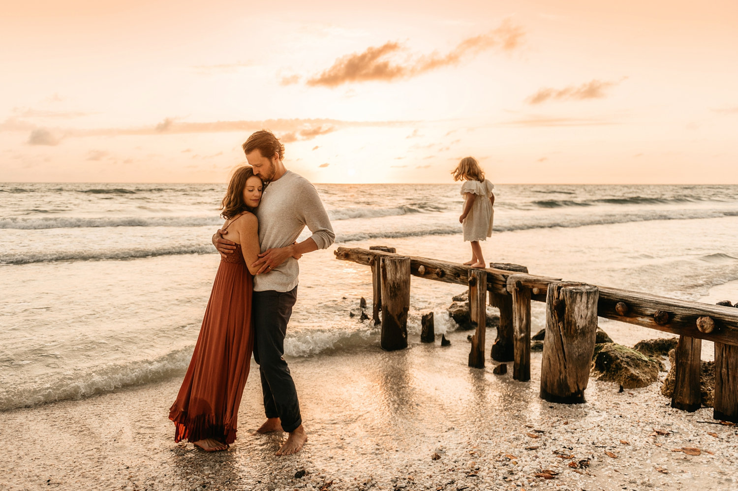 mom and dad hugging at the beach while little girl plays in background, Rya Duncklee Photos